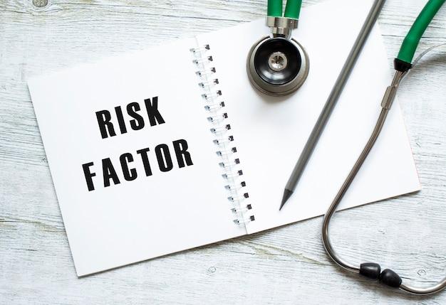 Risicofactoren is geschreven in een notitieboekje op een licht houten tafel naast een potlood en een stethoscoop