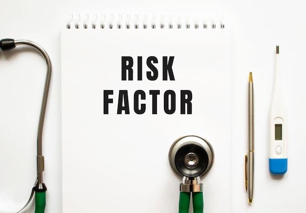 Risicofactoren tekst geschreven in een notitieboekje dat op een bureau ligt en een stethoscoop