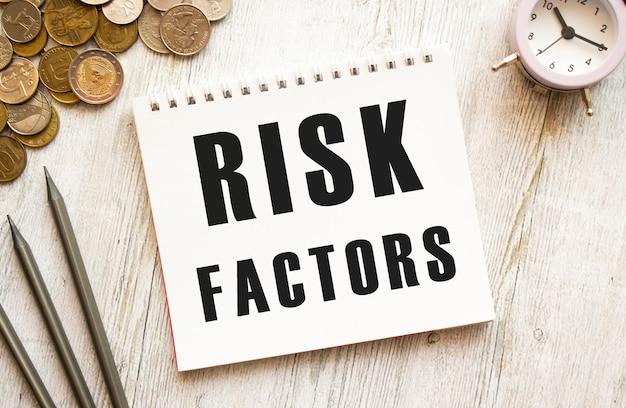 Risicofactoren tekst op een notitieblok munten staan verspreid