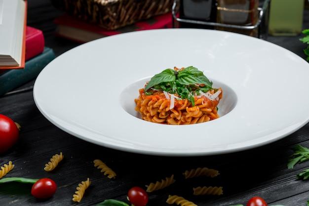 Risotto in tomatensaus met gehakte parmezaanse kaas en basilicumblaadjes bovenop