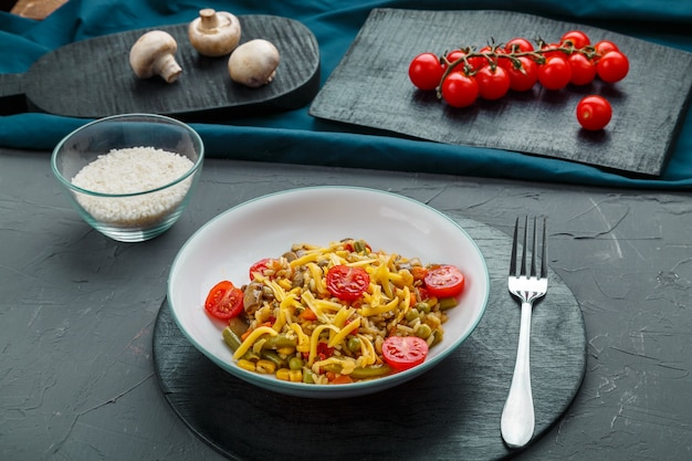 Risotto met champignons in een bord op een grijze achtergrond in de buurt van de ingrediënten op zwarte onderzetters en een vork. horizontale foto