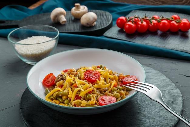 Risotto met champignons in een bord op een grijze achtergrond in de buurt van de ingrediënten op zwarte onderzetters en een vork.
