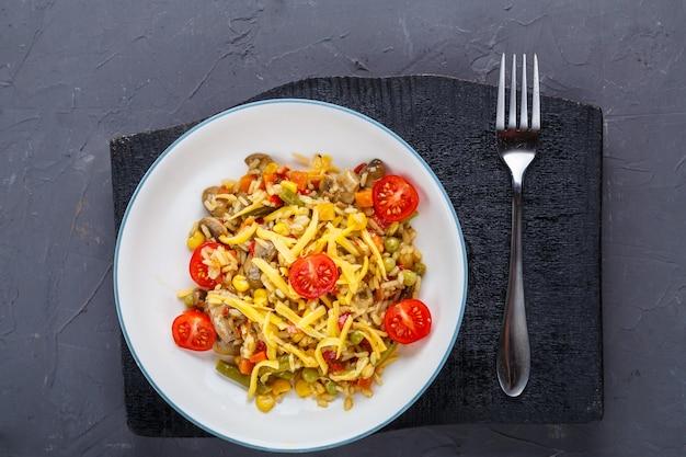 Risotto met champignons in een bord op een grijze achtergrond op zwarte onderzetters en een vork. horizontale foto