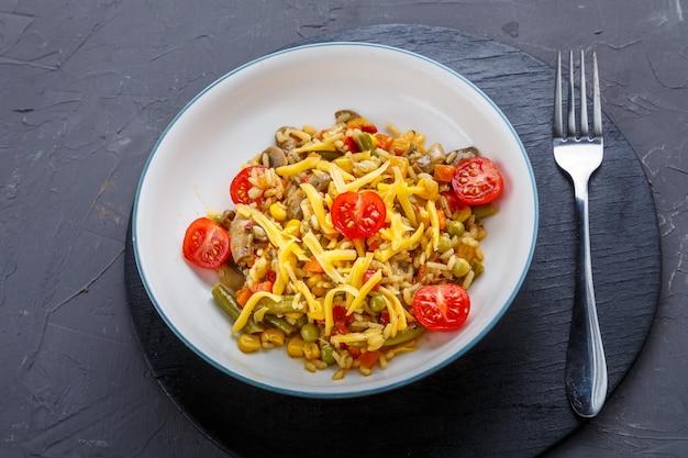 Risotto met champignons in een bord op een grijze achtergrond op zwarte onderzetters en een vork.