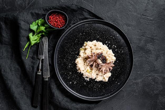 Risotto met octopus en champignons, peterselie en kruiden. zwarte achtergrond. bovenaanzicht. ruimte voor tekst