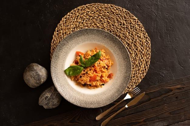Risotto met spek en tomaten, gegarneerd met basilicumblaadjes prachtig bewaard gebleven door bestek, bovenaanzicht.