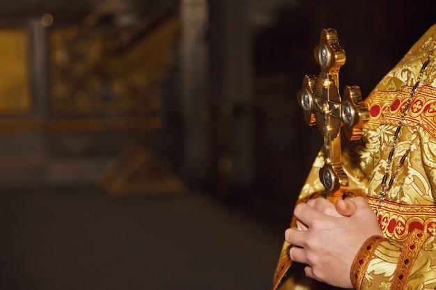 Rite van doopsel gouden kruis in priesterhanden in orthodoxe kerk of tempel voor ceremoniepasen