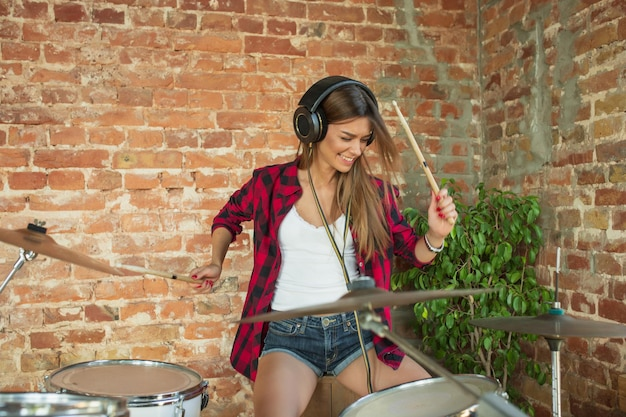 Ritme. thuismuziekstudio, mooie vrouw die muziek opneemt, zingt en drumt terwijl ze op de loft-werkplek of thuis zit. concept van hobby, muziek, kunst en creatie. eerste single maken.