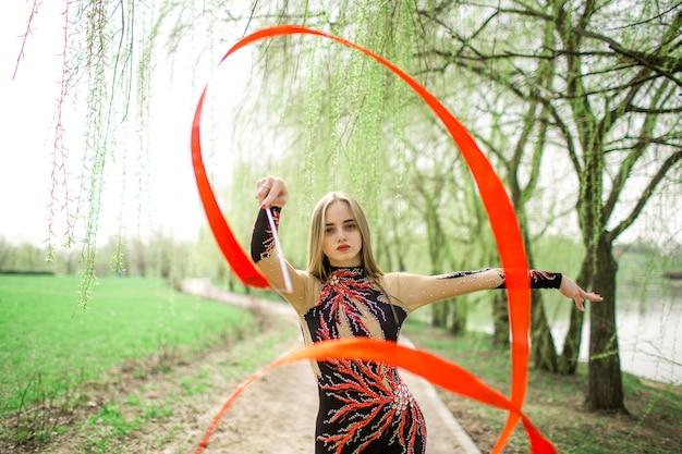 Ritmische gymnastiek. jong turnervrouwtje met rood lint openlucht in park