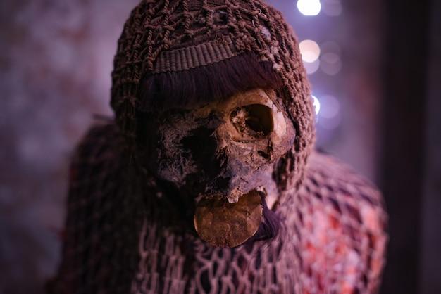 Ritueel mummie met een visnet op zijn hoofd en een oude munt in zijn mond.