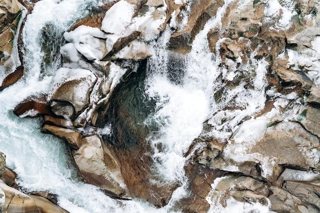 Rivier bij de berg. bovenaanzicht van de rotsen aan de onderkant van een heldere bergbeek. bruine rotsen en ruw water. stock foto