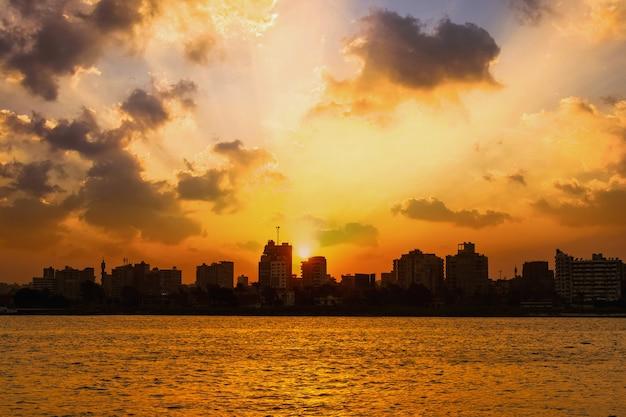 Rivier de nijl, de zon verbergt zich in de gebouwen van de stad caïro