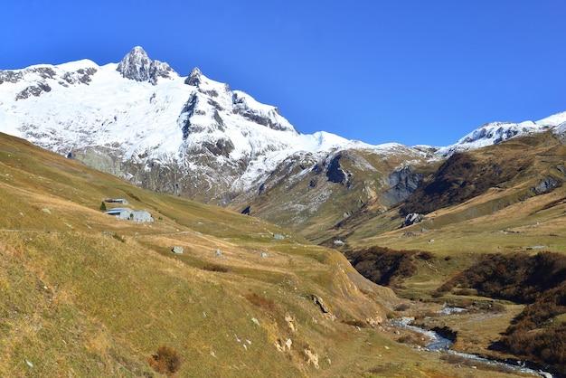 Rivier die alpiene vallei oversteekt met besneeuwde bergtop onder blauwe hemel
