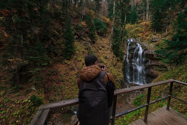 Rivier diep in bergbos. natuur samenstelling. mendelich rivier in de noordelijke kaukasus, rosa khutor, rusland, sochi. herfst bos, mist en regen. toerist maakt een foto van een waterval op een smartphone