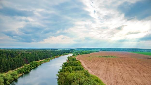 Rivier en platteland op bewolkte dag