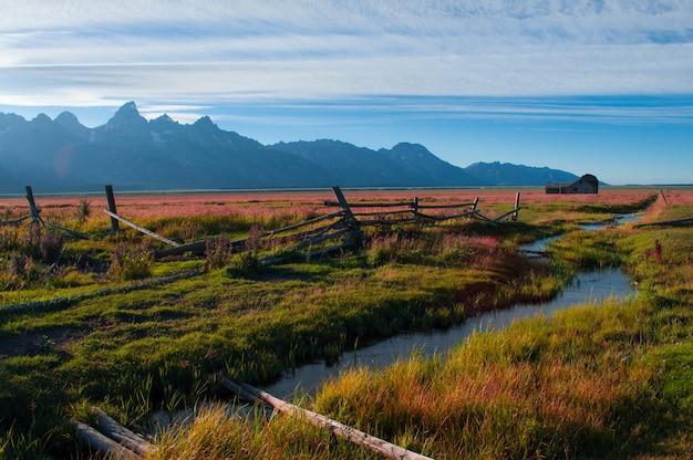 Rivier in het midden van een groen veld omgeven door een bergachtig landschap