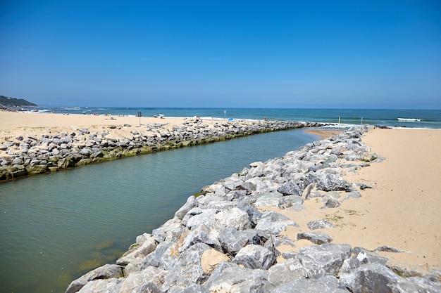 Rivier la uhabia stroomt in de oceaan met zandstrand in een kustplaats bidart, frankrijk