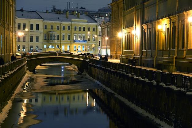 Rivier met reflecterende lantaarns en gebouwen in de winteravond