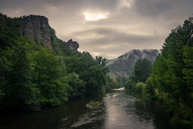 Rivier omgeven door rotsen bedekt met mossen en bossen onder het zonlicht en een bewolkte hemel