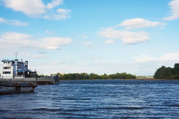 Rivier op een zonnige zomerdag met een mooie hemel in de wolken. links om de oude boot te zien.