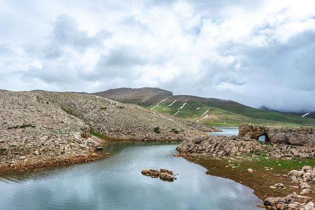 Rivier stroomt door rotsachtige heuvels. bewolkte dag