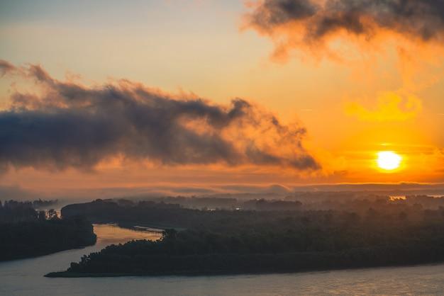 Rivier stroomt langs de kust met bos. kanaal stroomt rond het eiland in mist. oranje gloed rond zon bij dageraad in bewolkte hemel weerspiegeld water. ochtend sfeervol landschap van majestueuze natuur in tegenlicht.