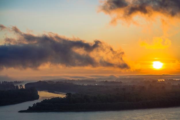 Rivier stroomt langs de kust met bos. kanaal stroomt rond het eiland in mist. oranje gloed rond zon bij dageraad in bewolkte hemel weerspiegeld water.
