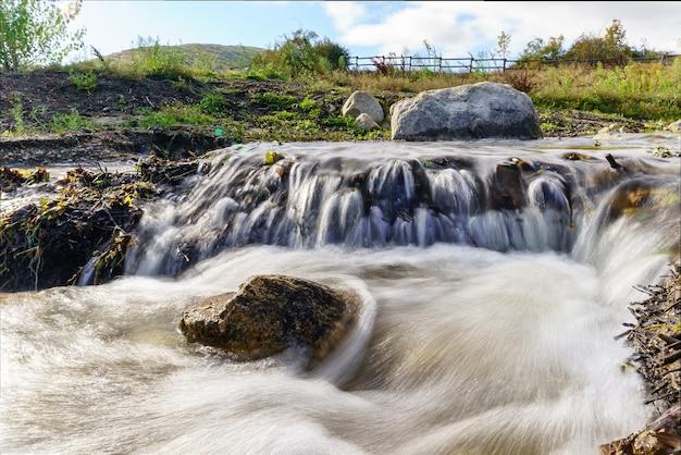Rivierlandschap met grote granieten rotsen gewassen door stromend water, wolken in de lucht en groene planten. foto groothoek, lange belichtingstijd. lozoya, madrid.