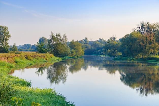Rivierlandschap op een achtergrond van blauwe hemel op zonnige zomerochtend