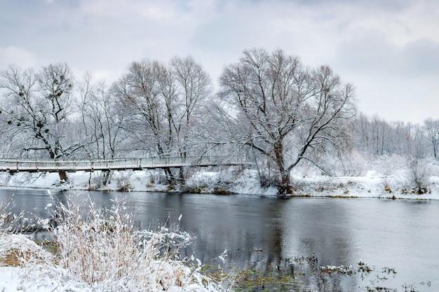 Rivieroever na een sneeuwval op een bewolkte winterdag. winter landschap