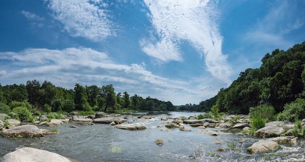 Rivierstroom van water in de rotsen met blauwe hemel