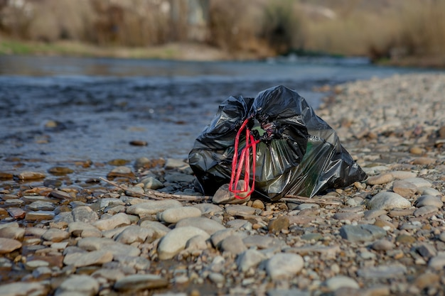 Riviervervuiling bij de kust, vuilniszak bij de rivier, plastic voedselafval