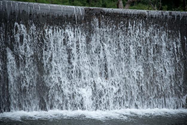 Rivierwater dat van dammuur valt