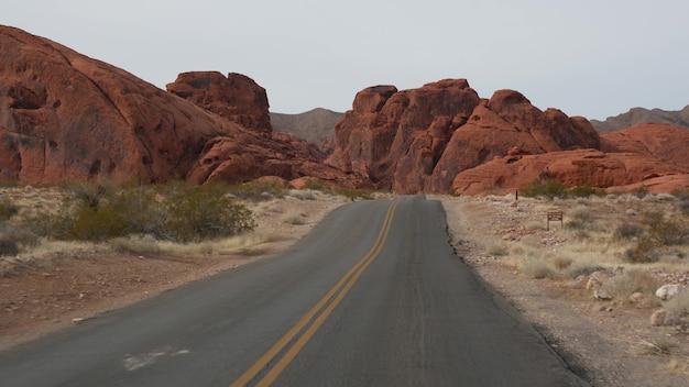 Road trip auto rijden in valley of fire las vegas nevada usa liften reizen in amerika snelweg reis rode buitenaardse rotsformatie mojave woestijn wildernis lijkt op mars uitzicht vanuit auto