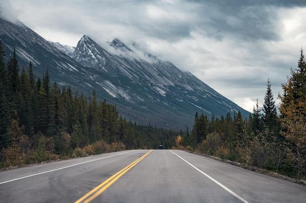 Road trip met rocky mountains in herfst bos op sombere in banff nationaal park