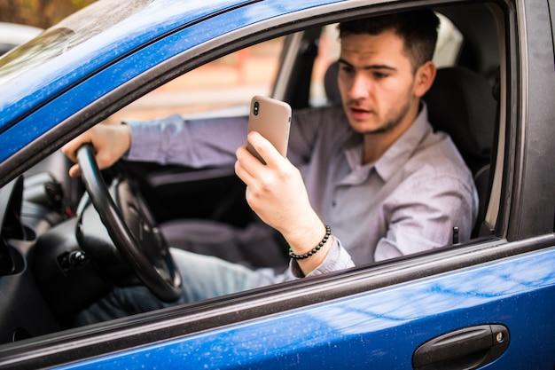 Road trip, transport, reizen, technologie en mensen concept. gelukkige glimlachende mens met smartphone het drijven in auto en het nemen van foto op telefoon