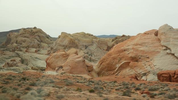 Roadtrip, autorijden in valley of fire, las vegas, nevada, vs. liftend reizen in amerika, snelwegreis. rode buitenaardse rotsformatie, mojave-woestijnwildernis lijkt op mars. uitzicht vanaf auto.