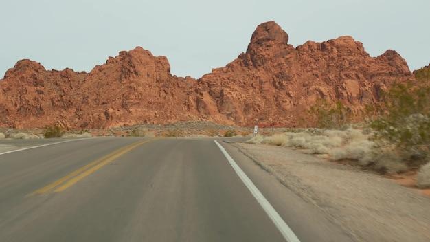 Roadtrip, autorijden in valley of fire, las vegas, nevada, vs. liftend reizen in amerika, snelwegreis. rode buitenaardse rotsformatie, mojave-woestijnwildernis lijkt op mars. uitzicht vanuit auto.