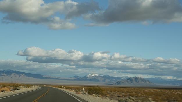 Roadtrip, autorijden van death valley naar las vegas, nevada, vs. liftend op reis in amerika. snelwegreis, dramatische sfeer, wolken, bergen en mojave-woestijnwildernis. uitzicht vanuit auto