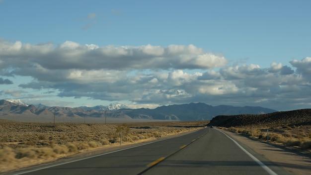 Roadtrip, autorijden van death valley naar las vegas, nevada, vs. liftend op reis in amerika. snelwegreis, dramatische sfeer, wolken, bergen en wildernis in de mojave-woestijn. uitzicht vanuit auto