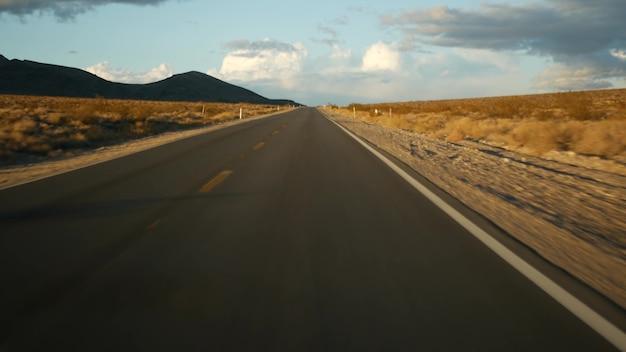 Roadtrip, autorijden van death valley naar las vegas, nevada, vs. liftend op reis in amerika. snelwegreis, dramatische sfeer, zonsondergangberg en mojave-woestijnwildernis. uitzicht vanaf auto.