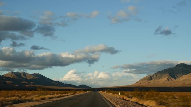 Roadtrip, autorijden van death valley naar las vegas, nevada, vs. liftend op reis in amerika. snelwegreis, dramatische sfeer, zonsondergangberg en mojave-woestijnwildernis. uitzicht vanuit auto.