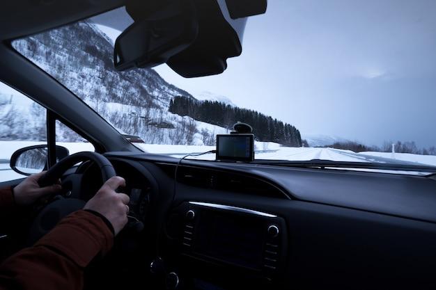 Roadtrip - man handen op het stuur en noorse bergen. lofoten eilanden. noorwegen.