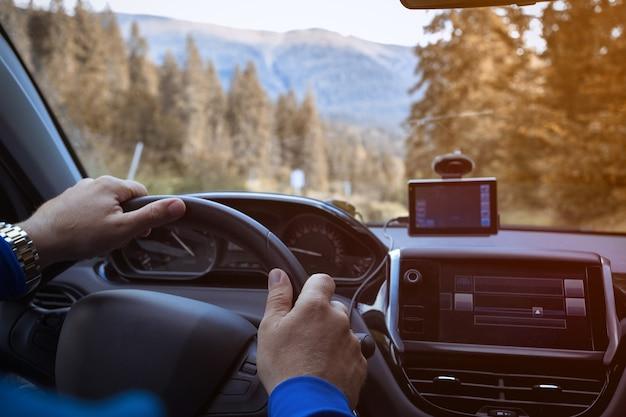 Roadtrip - mannenhanden aan het stuur en bergen op de achtergrond