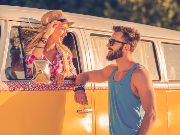 Roadtrip romantiek. mooie jonge vrouw die in een retro minibus zit en door het raam van het voertuig kijkt terwijl de man buiten staat en glimlacht