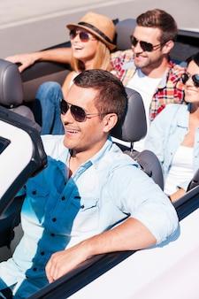 Roadtrippen met vrienden. bovenaanzicht van jonge gelukkige mensen die genieten van een roadtrip in hun witte cabrio