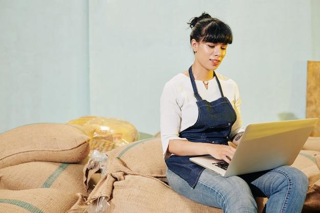 Roastery werknemer die op laptop werkt