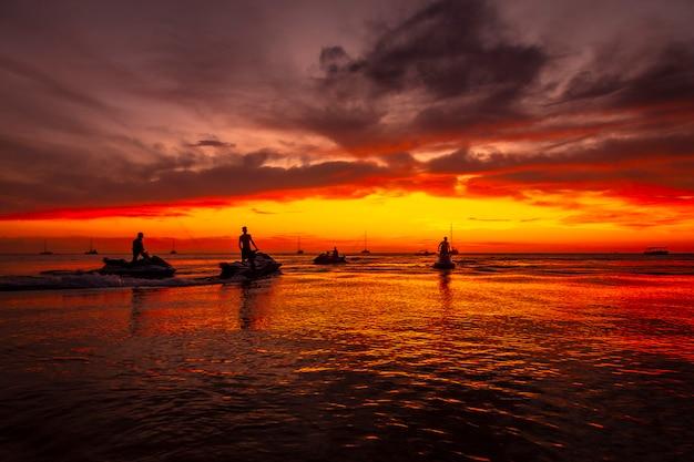 Roatan, honduras: een groep jonge mensen op een jetski bij zonsondergang op west end beach