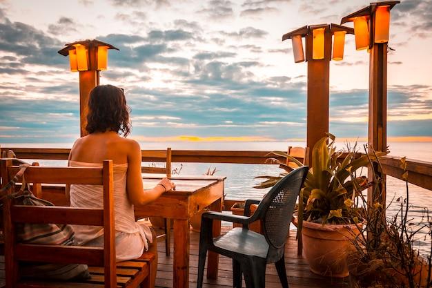 Roatán, honduras: een jonge vrouw in een west end-restaurant op het eiland roatan bij zonsondergang