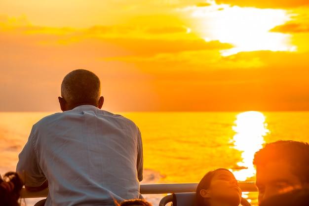 Roatan, honduras: een man die naar de zee kijkt bij zonsondergang op de veerboot naar roatan island